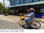 Купить «Local woman bicycling, Dong Hoa, Chau Thanh, Mekong Delta, Vietnam.», фото № 27329135, снято 6 апреля 2017 г. (c) age Fotostock / Фотобанк Лори