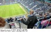 Купить «Болельщик на стадионе проходит через сектора стадиона к своему месту», видеоролик № 27332875, снято 9 ноября 2017 г. (c) Кекяляйнен Андрей / Фотобанк Лори