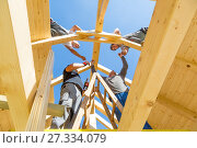 Builders at work with wooden roof construction. Стоковое фото, фотограф Matej Kastelic / Фотобанк Лори