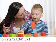 Купить «Child boy together with mother playing toys», фото № 27341371, снято 16 ноября 2018 г. (c) Оксана Кузьмина / Фотобанк Лори
