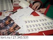 Купить «Помощник Санта Клауса - волшебный эльф готовит к отправке письма с новогодними пожеланиями Деду Морозу и Санта Клаусу в Почтовом отделении Волшебной почты на Тверской площади в Москве, Россия», фото № 27343531, снято 22 декабря 2017 г. (c) Николай Винокуров / Фотобанк Лори