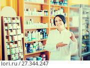 Купить «Smiling mature female seller holding supplement in box», фото № 27344247, снято 15 декабря 2018 г. (c) Яков Филимонов / Фотобанк Лори