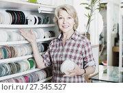 Купить «portrait of female customer standing next to different bands for sewing in shop», фото № 27345527, снято 22 марта 2019 г. (c) Яков Филимонов / Фотобанк Лори