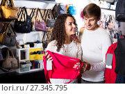 Купить «Female shopgirl helping young man to select handbag», фото № 27345795, снято 16 октября 2018 г. (c) Яков Филимонов / Фотобанк Лори