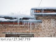 Купить «Ледяные сосульки свисают с карниза крыши дома. Зимняя оттепель», фото № 27347719, снято 6 января 2013 г. (c) Алёшина Оксана / Фотобанк Лори