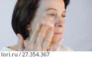 Купить «Middle aged woman applying cream on face», видеоролик № 27354367, снято 5 января 2018 г. (c) Илья Шаматура / Фотобанк Лори