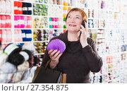 Купить «Woman with shopping bags using phone», фото № 27354875, снято 10 мая 2017 г. (c) Яков Филимонов / Фотобанк Лори