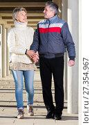 Купить «Glad adult husband and wife are walking together», фото № 27354967, снято 16 августа 2018 г. (c) Яков Филимонов / Фотобанк Лори