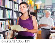 Купить «Teenage girl is choosing textbook for preparing to exam in bookstore.», фото № 27355131, снято 28 июня 2017 г. (c) Яков Филимонов / Фотобанк Лори