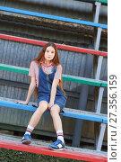 Задумчивая длинноволосая красивая девушка-подросток в джинсовом сарафане сидит на разноцветной трибуне. Стоковое фото, фотограф Наталья Гармашева / Фотобанк Лори