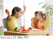 Купить «Cute smiling child and toddler girls playing and eating spaghetti with vegetables for healthy lunch sitting in a white sunny kitchen with big window», фото № 27356707, снято 29 ноября 2017 г. (c) Оксана Кузьмина / Фотобанк Лори