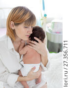 Купить «Mom hugging her sleeping newborn baby in hands», фото № 27356711, снято 8 ноября 2017 г. (c) Оксана Кузьмина / Фотобанк Лори