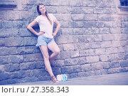 Купить «Young woman on old stone wall background», фото № 27358343, снято 15 августа 2017 г. (c) Яков Филимонов / Фотобанк Лори