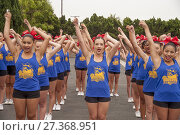 Купить «A multiracial high school pep squad limbers up before marching in a city anniversary parade in Fountain Valley, CA.», фото № 27368951, снято 24 июня 2017 г. (c) age Fotostock / Фотобанк Лори