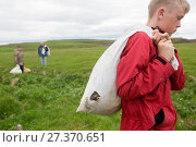 Купить «Boy  with bag of Common eider duck (Somateria mollissima) down collected from breeding birds, Flatey, Iceland.  Highly commended in the Man and Nature...», фото № 27370651, снято 21 сентября 2018 г. (c) Nature Picture Library / Фотобанк Лори