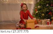 Купить «happy girl opening christmas gift at home», видеоролик № 27377775, снято 27 декабря 2017 г. (c) Syda Productions / Фотобанк Лори
