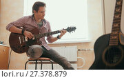 Купить «Attractive young musician composes music on the guitar and plays, other musical instrument in the foreground», видеоролик № 27378879, снято 16 июля 2018 г. (c) Константин Шишкин / Фотобанк Лори