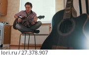 Купить «Young guy musician composes music on the guitar and plays in the kitchen, other musical instrument in the foreground,», видеоролик № 27378907, снято 23 сентября 2018 г. (c) Константин Шишкин / Фотобанк Лори