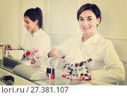 Купить «Female manicurist showing lacquer color schemes», фото № 27381107, снято 2 февраля 2017 г. (c) Яков Филимонов / Фотобанк Лори