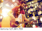 Купить «couple of musicians with guitar at music store», фото № 27381759, снято 11 декабря 2014 г. (c) Syda Productions / Фотобанк Лори