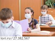Купить «School kids with protection mask against flu virus at lesson in classroom», фото № 27382567, снято 20 января 2018 г. (c) Оксана Кузьмина / Фотобанк Лори