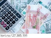 Купить «On the table there are money Russian rubles and a calculator. Calculation of profit», фото № 27385191, снято 6 января 2018 г. (c) Катерина Белякина / Фотобанк Лори