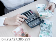 The girl at the table considers the profit with the calculator. Стоковое фото, фотограф Катерина Белякина / Фотобанк Лори