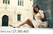 Купить «young happy female in rose dress sitting in city», видеоролик № 27385403, снято 8 сентября 2017 г. (c) Яков Филимонов / Фотобанк Лори