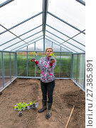 Купить «Pretty woman with cucumber sprouts stands inside the greenhouse», фото № 27385891, снято 14 июня 2014 г. (c) Евгений Ткачёв / Фотобанк Лори
