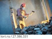 worker with sledgehammer at indoor wall destroying. Стоковое фото, фотограф Дмитрий Калиновский / Фотобанк Лори