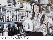 Купить «Happy saleswoman offering electric kettle», фото № 27387915, снято 12 декабря 2017 г. (c) Яков Филимонов / Фотобанк Лори