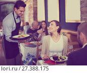 Купить «Waiter male bringing food for man and woman guests», фото № 27388175, снято 11 декабря 2017 г. (c) Яков Филимонов / Фотобанк Лори