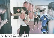 Купить «Sporty girl is boxing near punching bag in gym.», фото № 27388223, снято 8 октября 2017 г. (c) Яков Филимонов / Фотобанк Лори