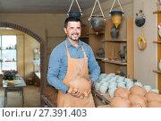 Купить «nice man potter holding ceramic vessels», фото № 27391403, снято 20 октября 2018 г. (c) Яков Филимонов / Фотобанк Лори