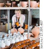 Купить «Portrait of glad woman pottery worker with ceramic crockery», фото № 27391407, снято 19 августа 2018 г. (c) Яков Филимонов / Фотобанк Лори