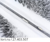 Купить «Два грузовых автомобиля на зимней лесной трассе, вид сверху», фото № 27403507, снято 10 января 2018 г. (c) Кекяляйнен Андрей / Фотобанк Лори