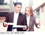 Купить «Young businessman and his colleague with coffee are reading docu», фото № 27404191, снято 20 августа 2017 г. (c) Яков Филимонов / Фотобанк Лори