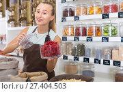 Купить «Young woman is offering dried flowers of Hibiscus in container», фото № 27404503, снято 4 сентября 2017 г. (c) Яков Филимонов / Фотобанк Лори
