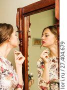 Купить «Девушка в красивом платье смотрится в зеркало / Снимок сделан в интерьере частного дома», фото № 27404679, снято 7 января 2018 г. (c) Вадим Орлов / Фотобанк Лори