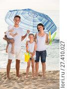 Купить «family under sun umbrella on the beach», фото № 27410027, снято 23 апреля 2019 г. (c) Яков Филимонов / Фотобанк Лори