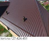 Купить «Air ducts on metal roof. The roof of corrugated sheet. Roofing o», фото № 27424451, снято 10 сентября 2017 г. (c) Леонид Еремейчук / Фотобанк Лори