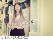 Купить «seller showing refrigerator», фото № 27425627, снято 12 декабря 2017 г. (c) Яков Филимонов / Фотобанк Лори