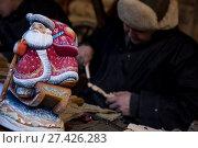 Купить «Мастер вырезает игрушку из дерева на фоне готовой деревянной игрушки деда Мороза», фото № 27426283, снято 31 декабря 2017 г. (c) Николай Винокуров / Фотобанк Лори