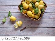 Купить «Fresh, ripe, collected lemons in a woven basket on a wooden table close-up», фото № 27426599, снято 21 января 2018 г. (c) Татьяна Ляпи / Фотобанк Лори