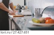 Купить «Male chef preparing salad in commercial kitchen - cuts the onion», фото № 27427651, снято 15 августа 2018 г. (c) Константин Шишкин / Фотобанк Лори