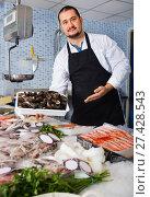 Купить «Seller stands behind counter with big mussels», фото № 27428543, снято 27 октября 2016 г. (c) Яков Филимонов / Фотобанк Лори