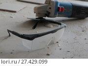 Купить «Защитные очки лежат на фоне болгарки и кафельных плиток», фото № 27429099, снято 22 января 2018 г. (c) Мария Ярошко / Фотобанк Лори