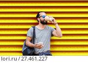 Купить «man with smartphone drinking coffee over wall», фото № 27461227, снято 2 июня 2016 г. (c) Syda Productions / Фотобанк Лори