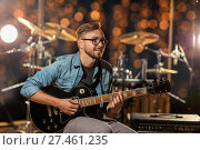 Купить «musician playing guitar at studio over lights», фото № 27461235, снято 18 августа 2016 г. (c) Syda Productions / Фотобанк Лори