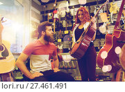 Купить «couple of musicians with guitar at music store», фото № 27461491, снято 11 декабря 2014 г. (c) Syda Productions / Фотобанк Лори